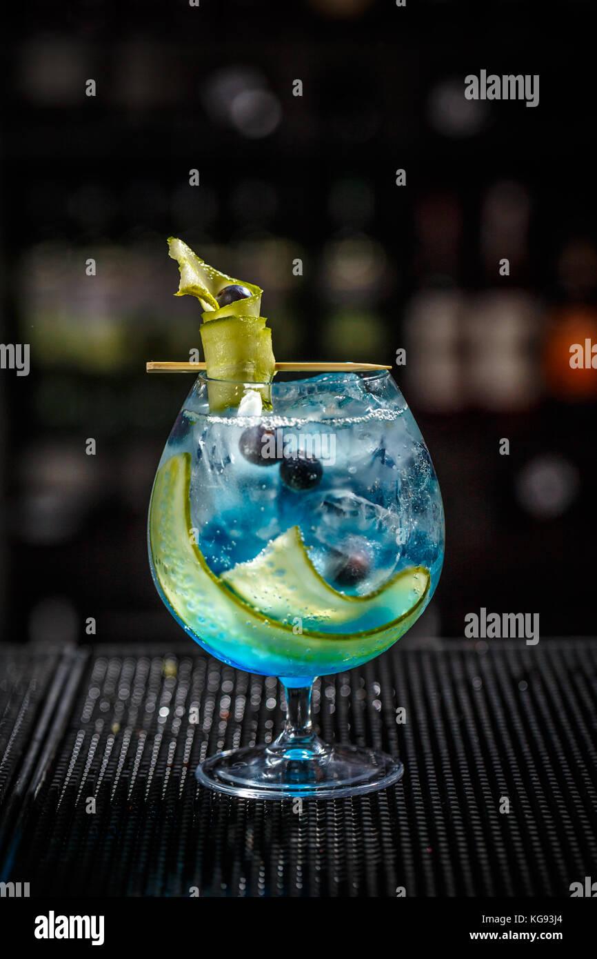 Blue Gin Tonic mit Gurke auf der Theke serviert. Stockbild