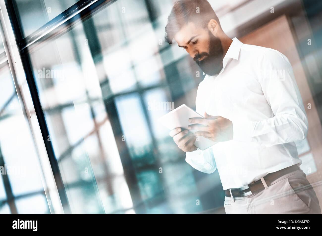 Hübscher junger Geschäftsmann über seine digitalen Tablet Stockbild