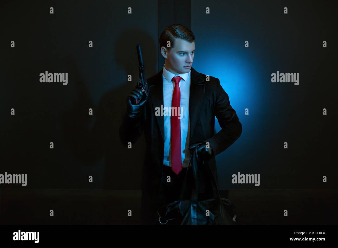 Der Mensch ist ein Mörder mit einer Pistole in der Hand in der Nacht. Stockbild