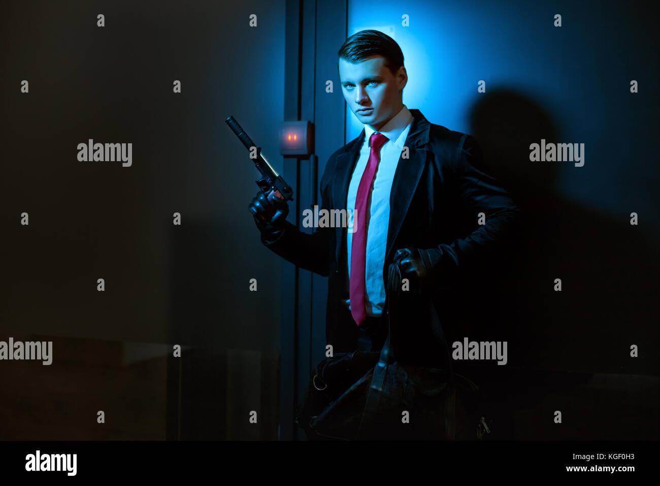 Menschen mit einem Beruf ist ein Mörder, in der Hand eine Pistole mit Schalldämpfer. Stockbild