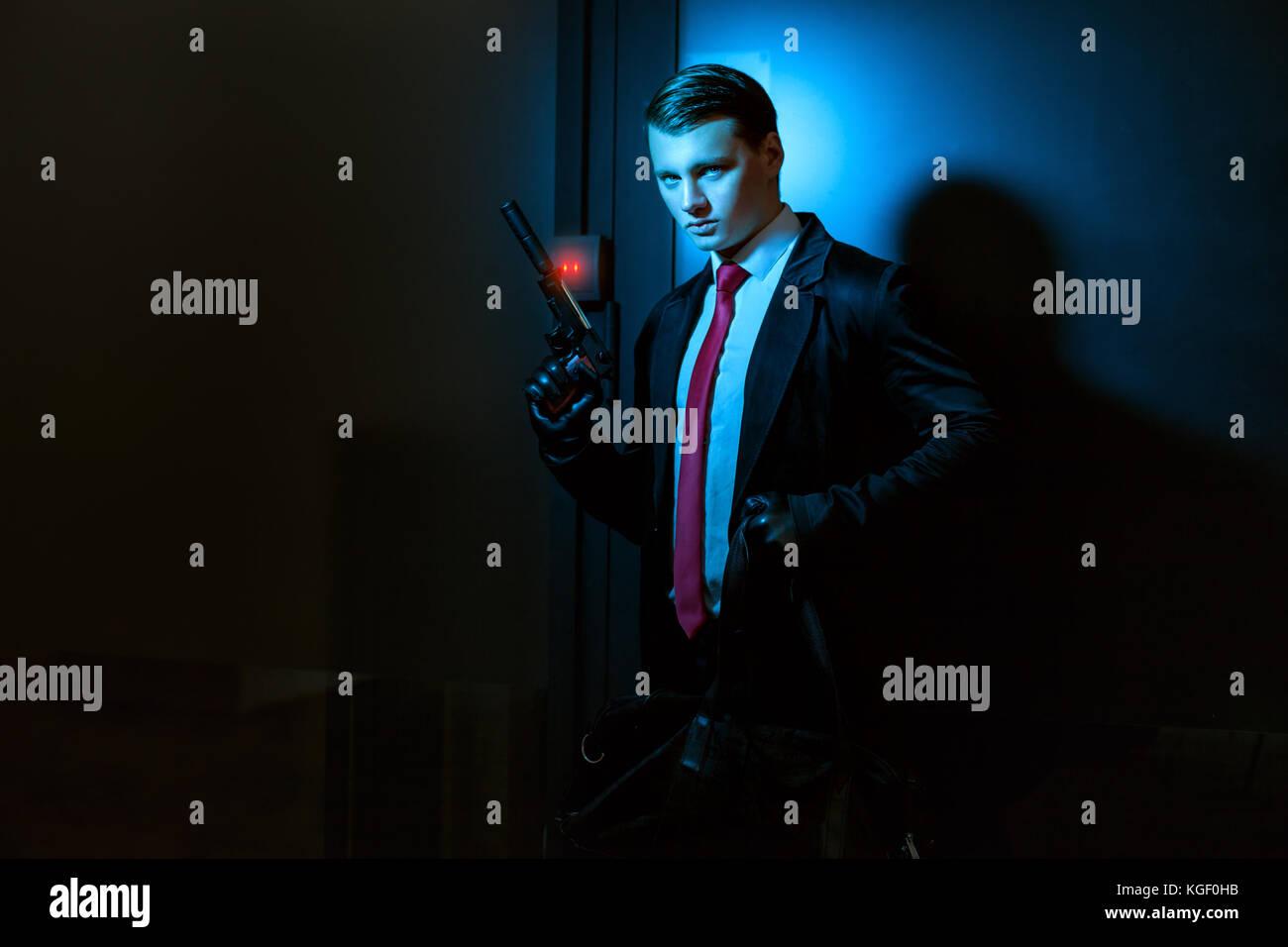 Mann mit Handschuhen und einem Gewehr, er ist ein professioneller Killer, seine Pistole mit Schalldämpfer. Stockbild