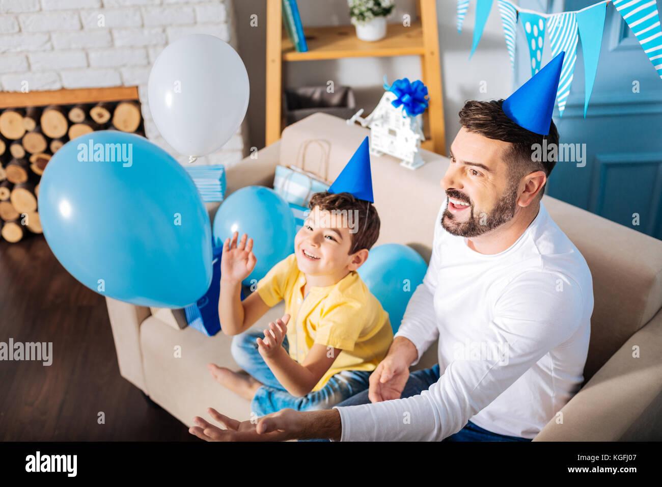 Gerne Vater und Sohn spielen mit Ballons am Geburtstag Stockbild