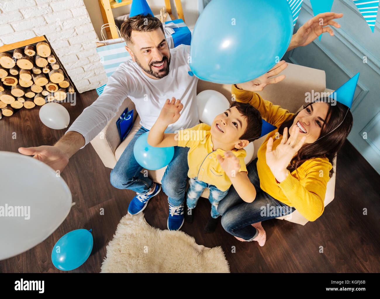 Freudige Familie werfen Luftballons während der Geburtstagsfeier Stockbild