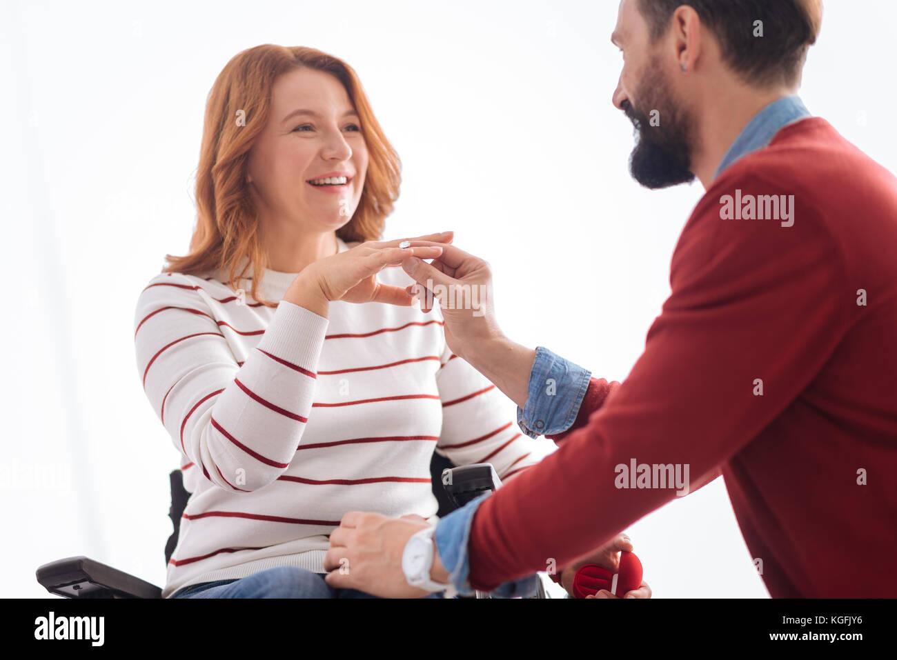 Mann, einen Ring an seine glückliche Bräute Finger Stockbild