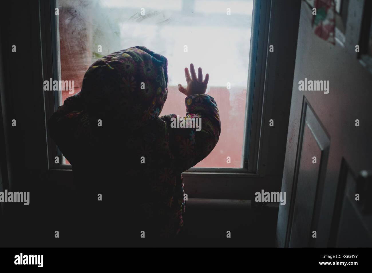 Ein kleines Mädchen sieht aus dem Fenster bei kaltem Wetter Stockbild