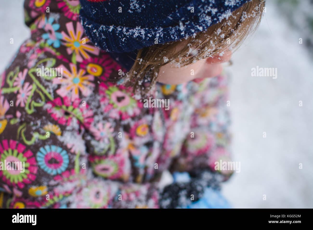 Ein Kleinkind steht außerhalb der Kleidung tragen im Winter mit Schnee um sie herum. Stockbild