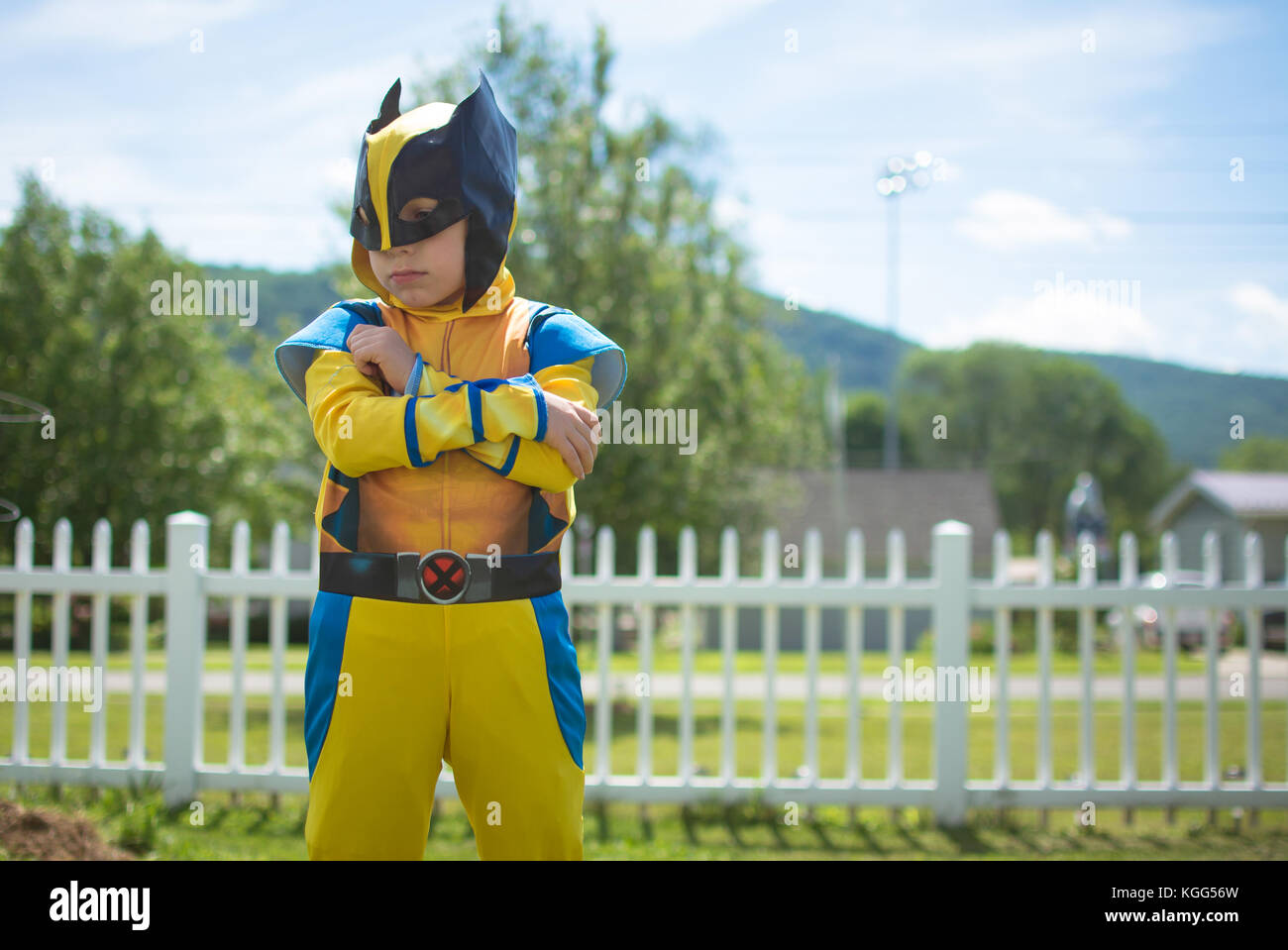 Ein Junge trägt ein Kostüm, außerhalb mit verschränkten Armen Stockbild