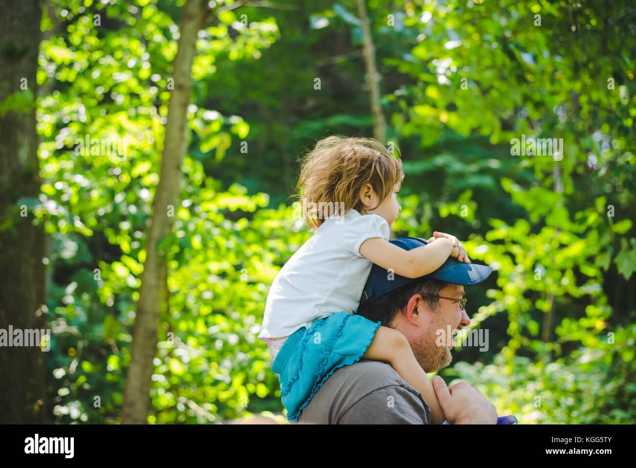 Ein Vater trägt seine Tochter auf seinen Schultern Stockbild