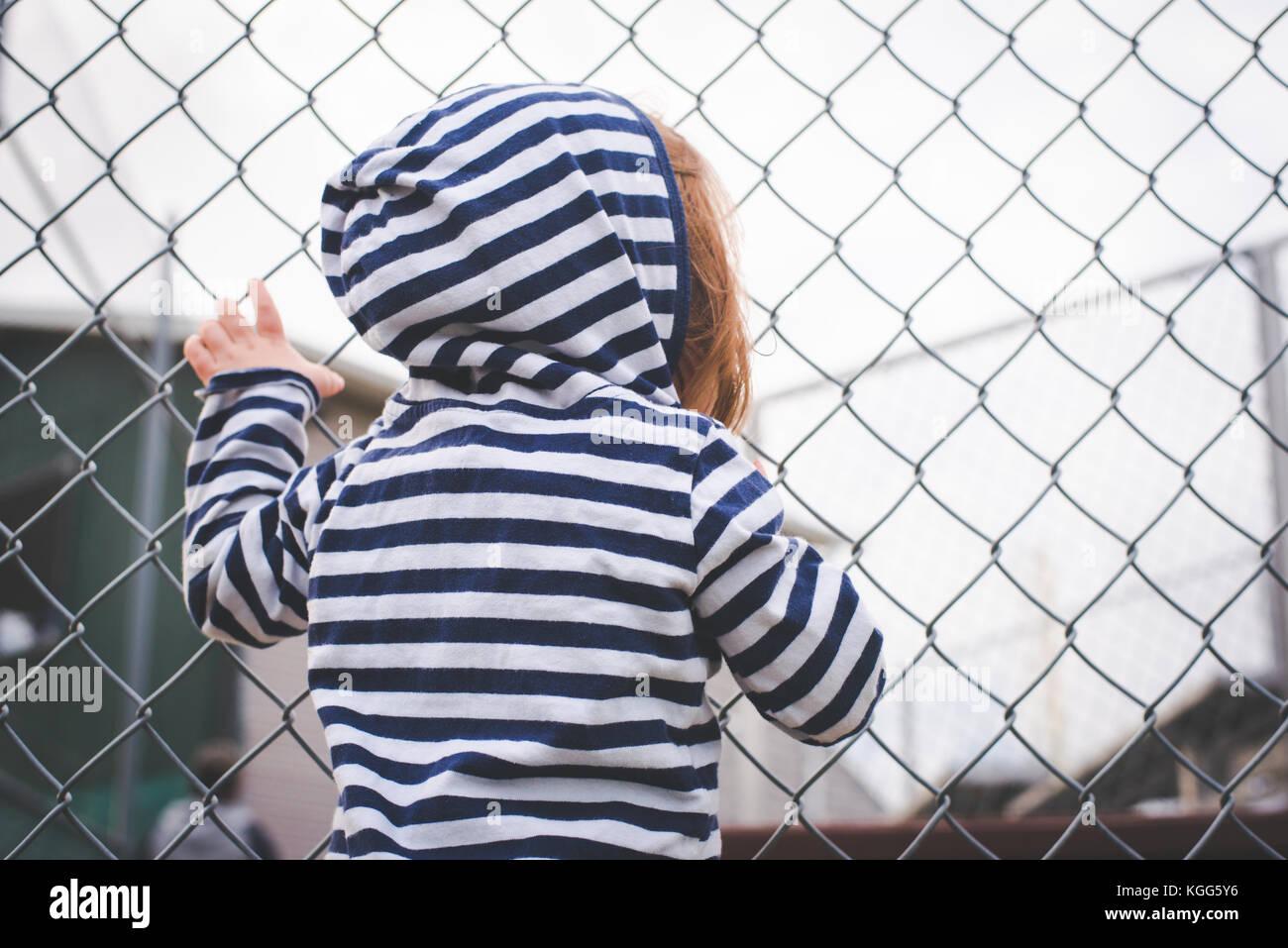 Kind hängt an einem Zaun und sieht durch sie hindurch. Stockbild