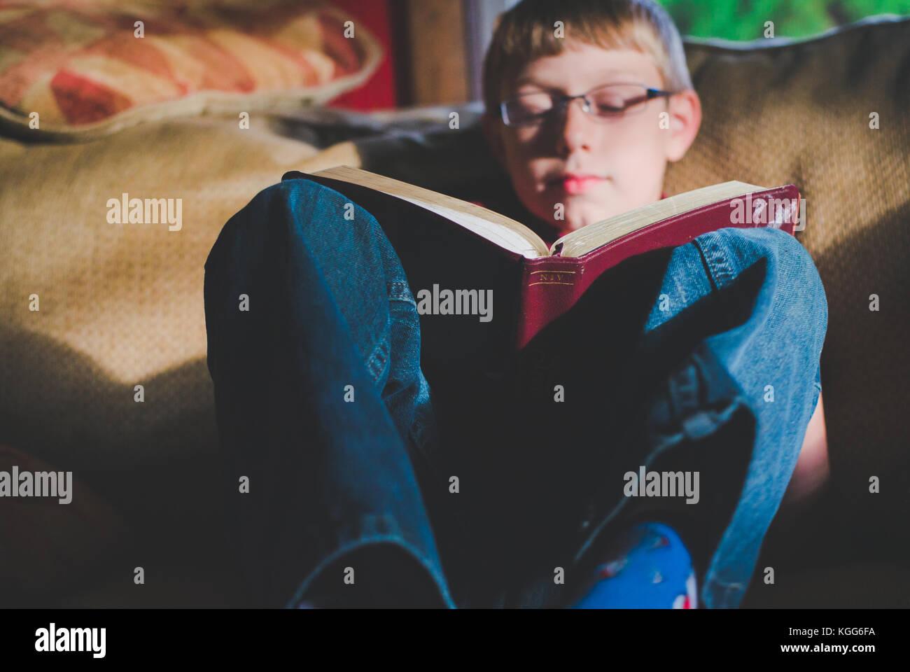 10-11 Jahre alter Junge, ein Buch zu lesen Stockfoto