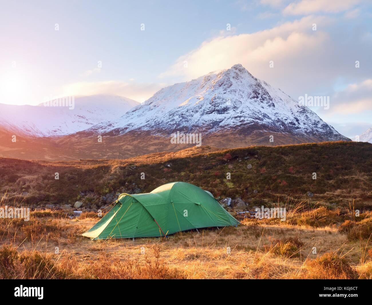 Grüne touristischen Zelt auf der Wiese am Fluss unter schneebedeckten Kegel von Berg Stob Dearg 1021 Meter Stockbild