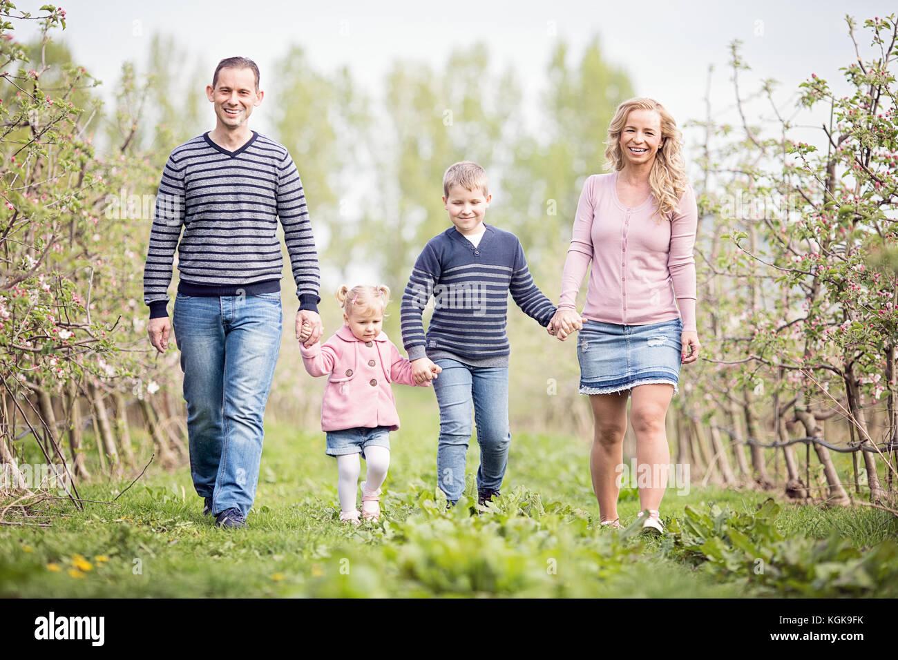 Glückliche junge 4 köpfige Familie zusammen im Freien im Orchard Stockfoto