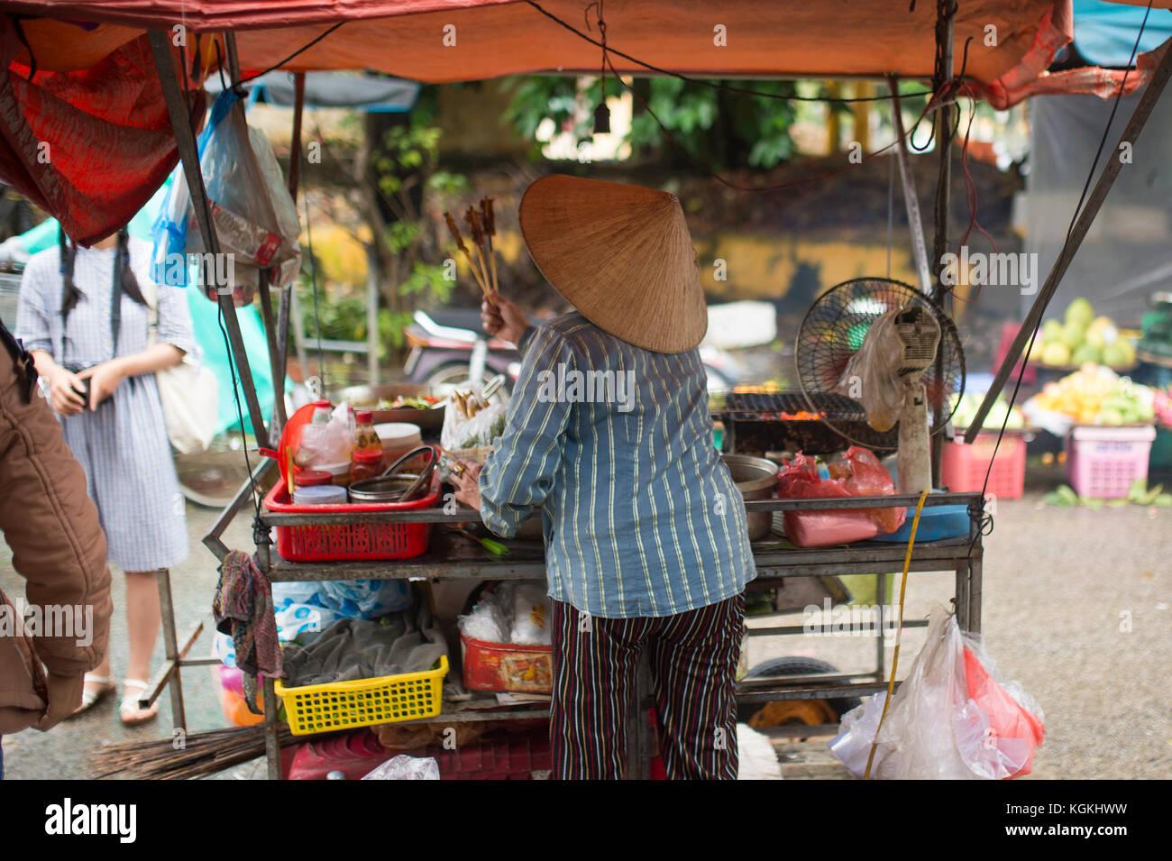 - Selektiver Fokus - nicht identifizierte Frau mit typischen vietnamesischen konischen Hüten verkaufen frisches Gemüse und Fleisch Spieße auf einem Straßenmarkt in Hoi An, Vietnam Stockfoto