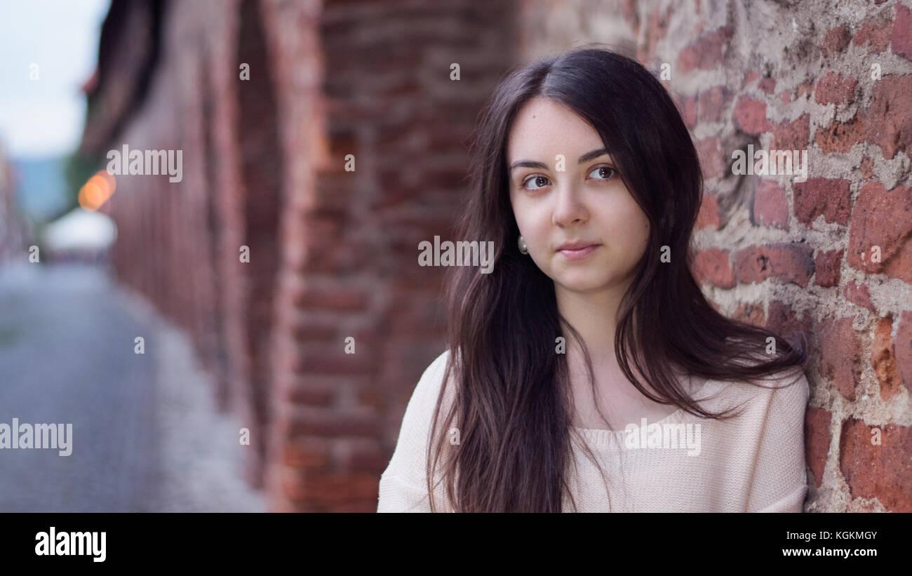 Porträt einer jungen Frau gegen eine mittelalterliche Mauer in Europa, Rumänien Stockbild