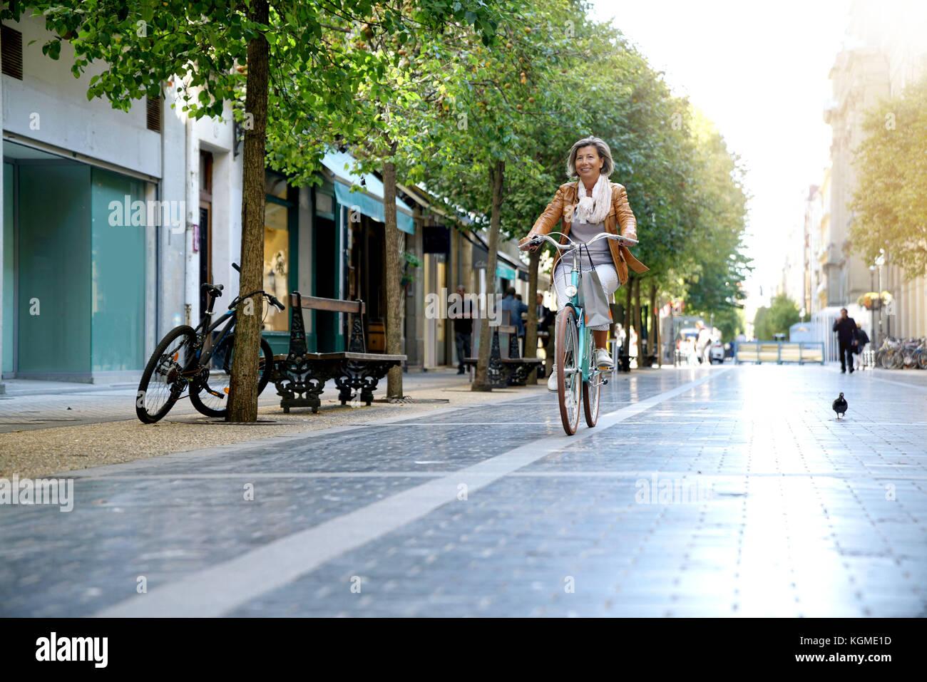 Ältere Frau reiten City Bike in der Stadt Stockbild