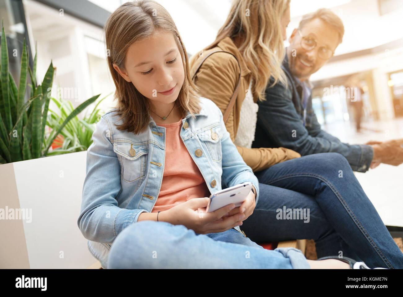 Familie auf Shopping Tag in der Mall, sitzen auf den öffentlichen Prüfstand Stockbild