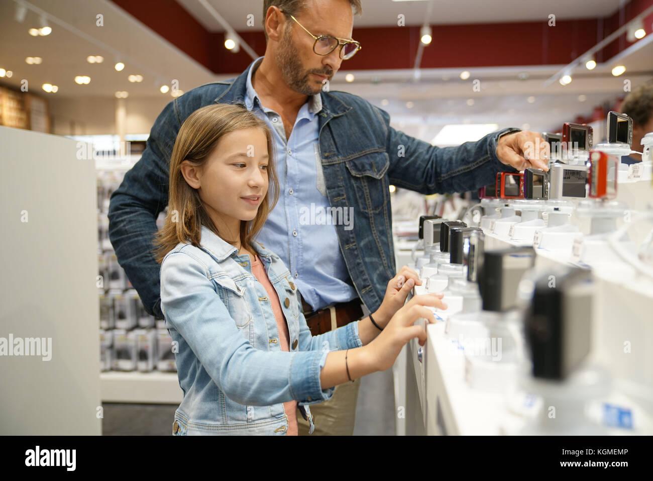 Mann mit Kind auf der Suche nach kompakten Kameras in Multimedia store Stockbild