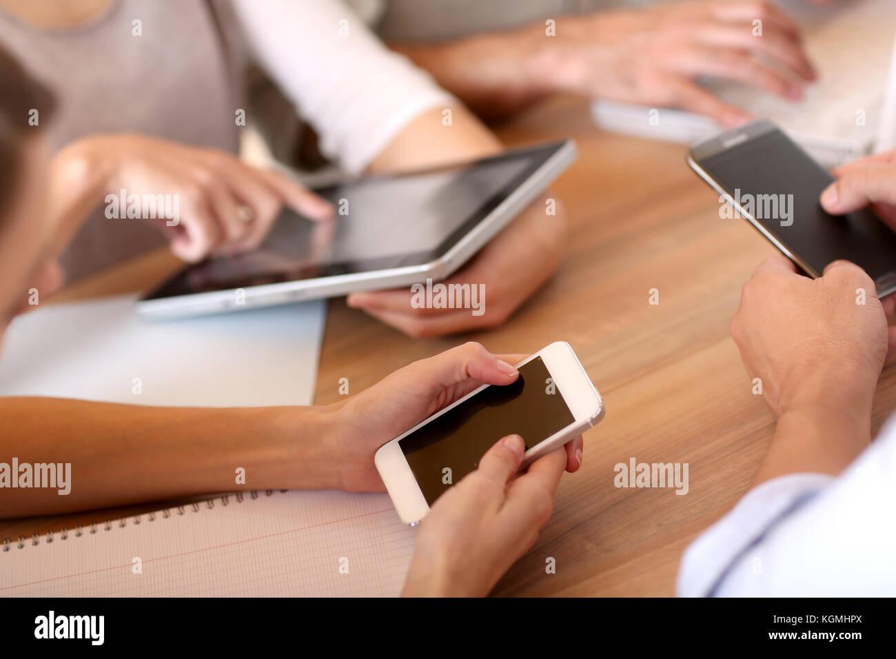 Gruppe von Geschäftsleuten mit elektronischen Geräten bei der Arbeit Stockbild