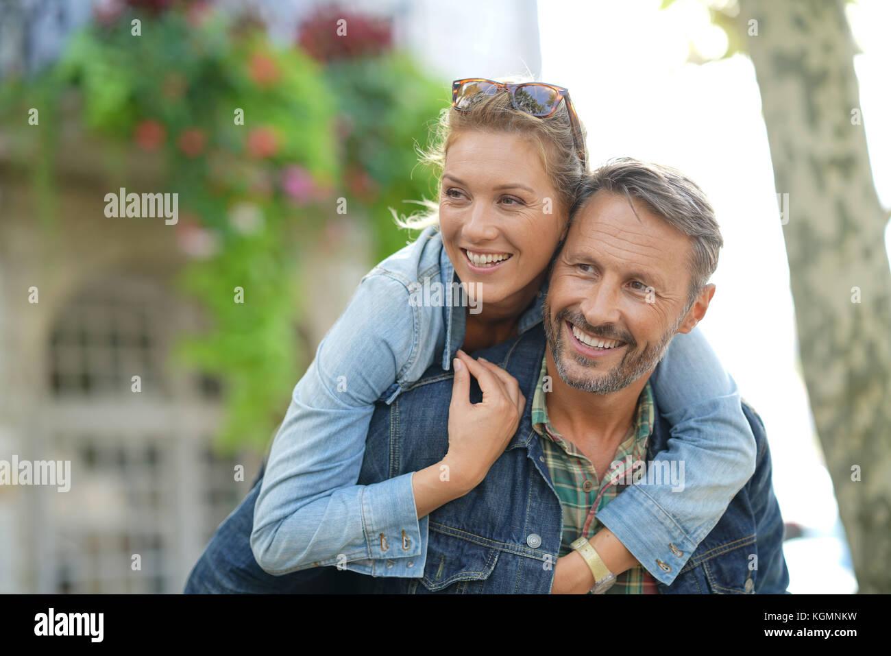 Mann, piggyback Ride zu Frau Stockbild