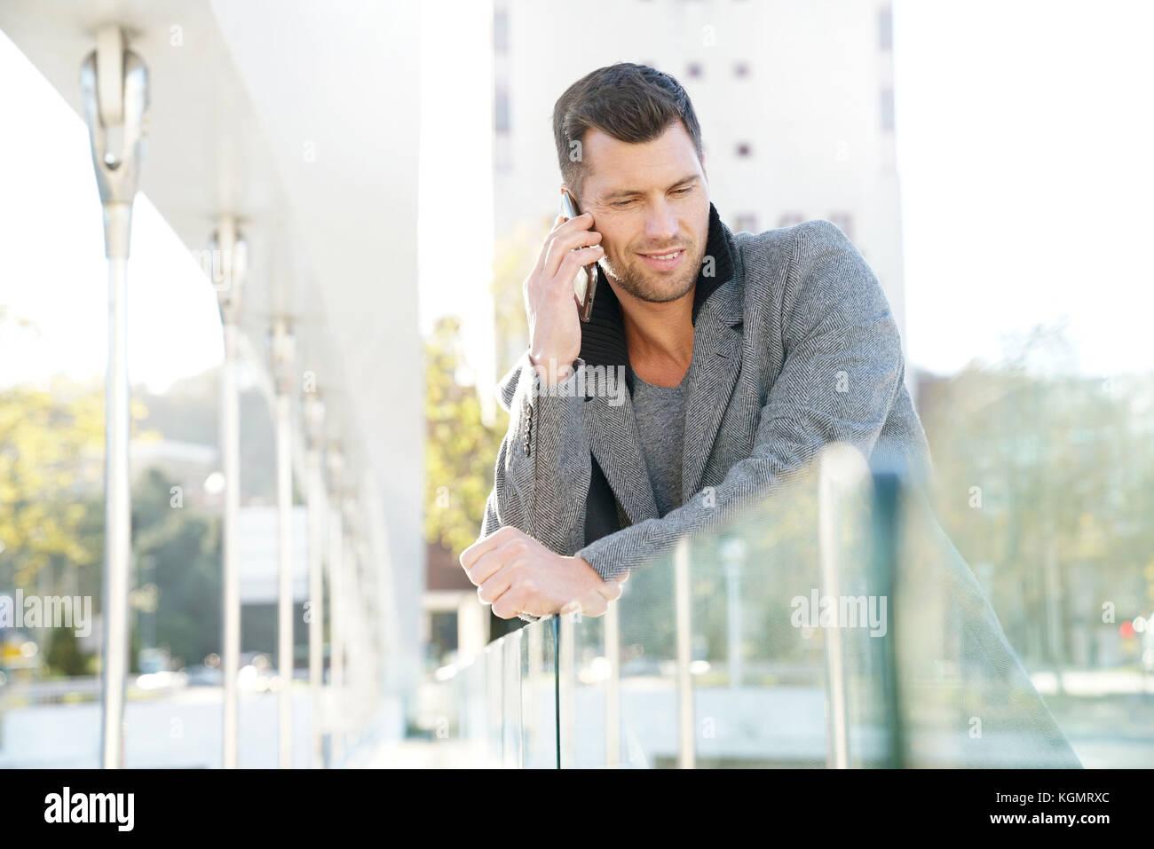 Gut aussehender Geschäftsmann außerhalb am Telefon sprechen Stockbild