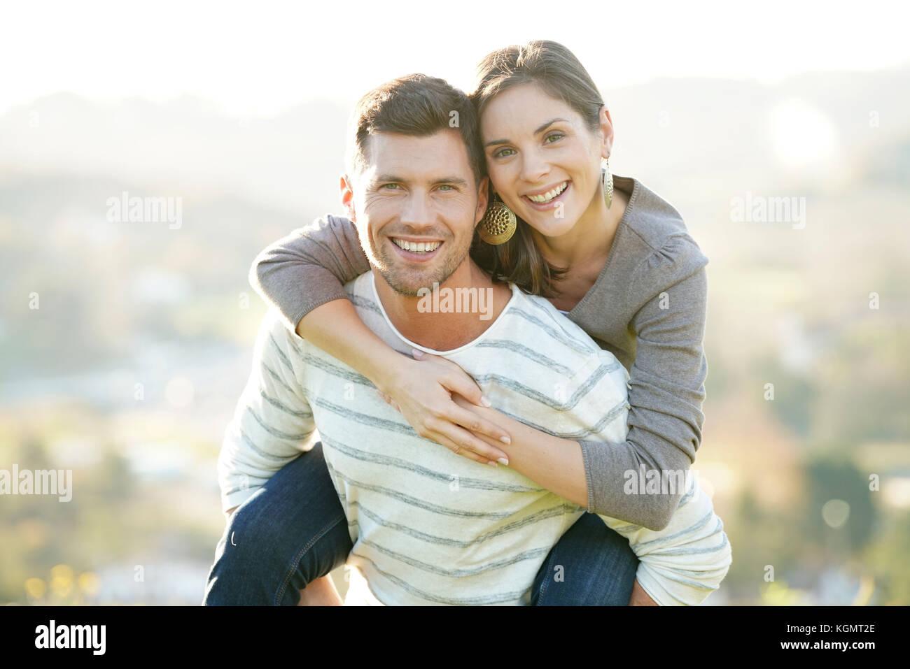 Portrait von fröhlicher Mann, der piggyback Ride zu Freundin Stockbild