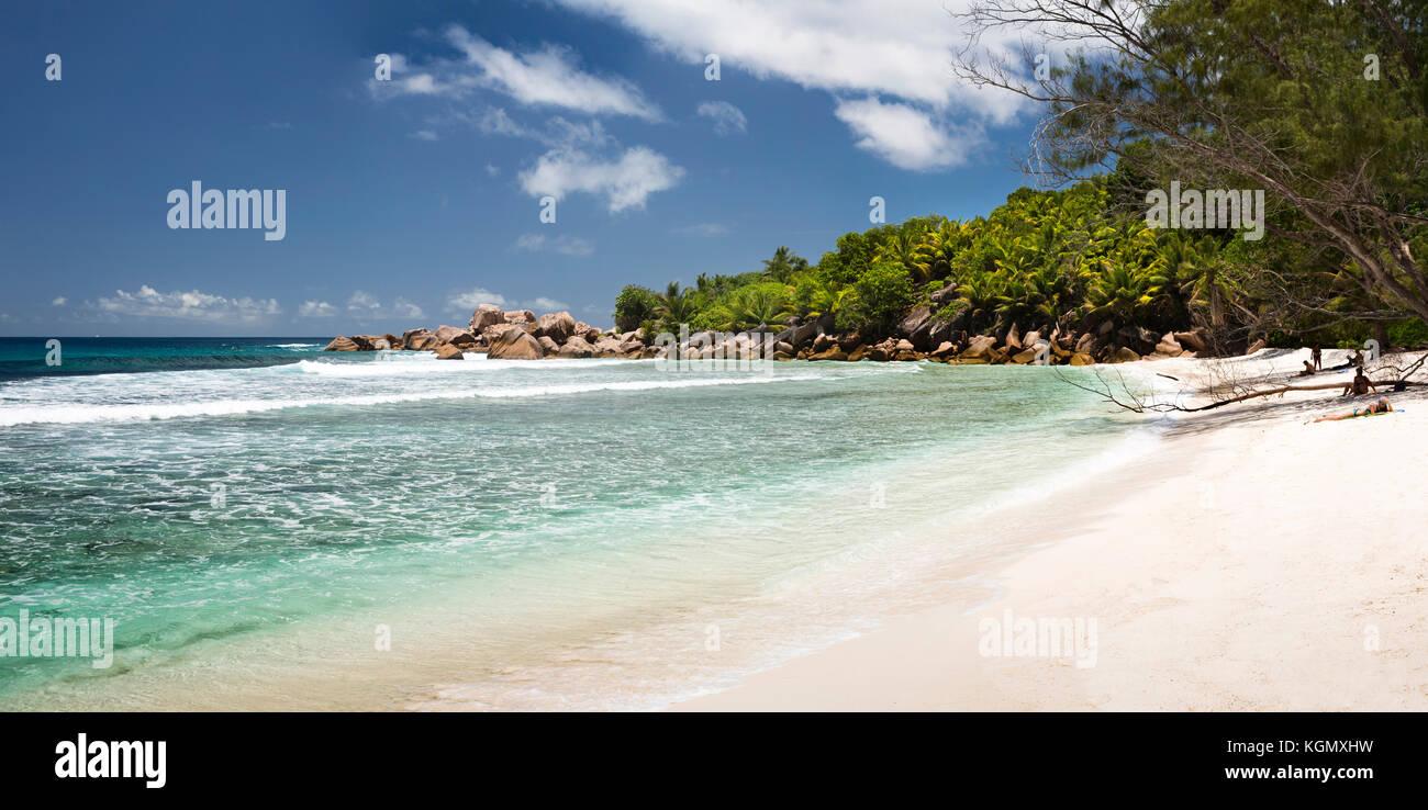 Die Seychellen, La Digue, Anse Cocos, Touristen Sonnenbaden auf idyllischen tropischen Strand Stockbild