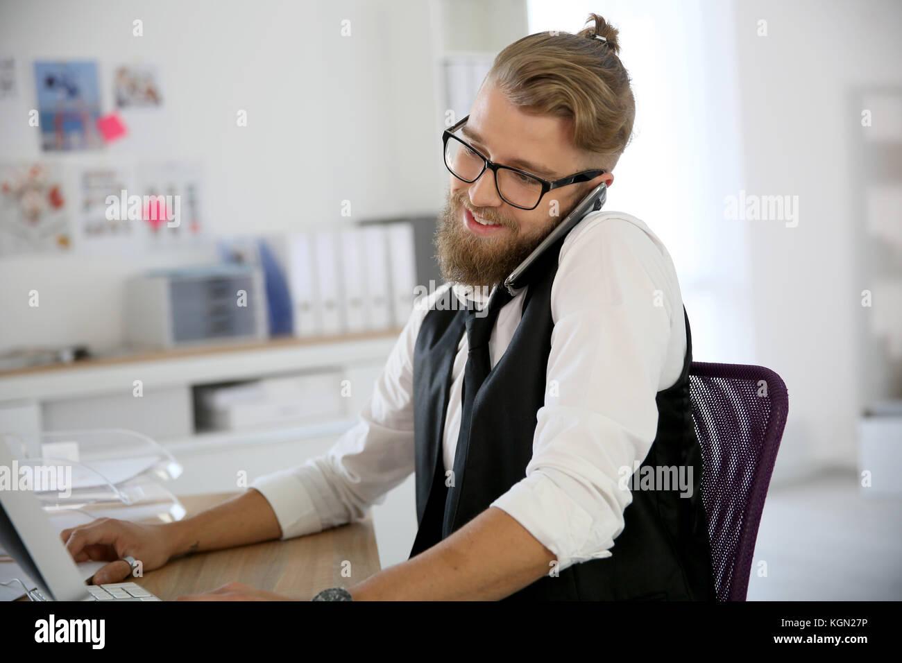 Junge Designer im Büro am Telefon sprechen Stockbild