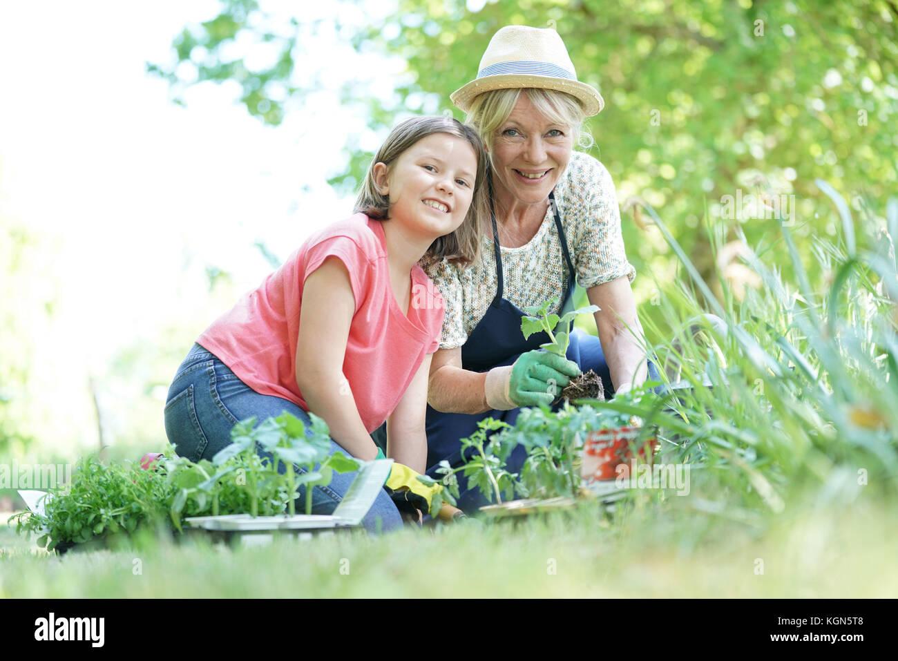 Großmutter und Enkelin zusammen im Garten Stockbild