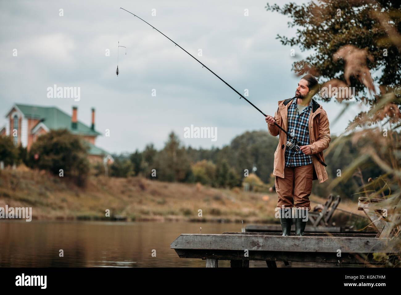 Mann Angeln mit Rute am See Stockbild