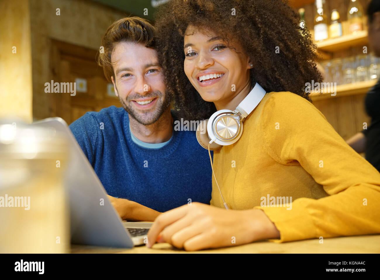 Paar im Restaurant auf Internet mit Laptop angeschlossen Stockbild