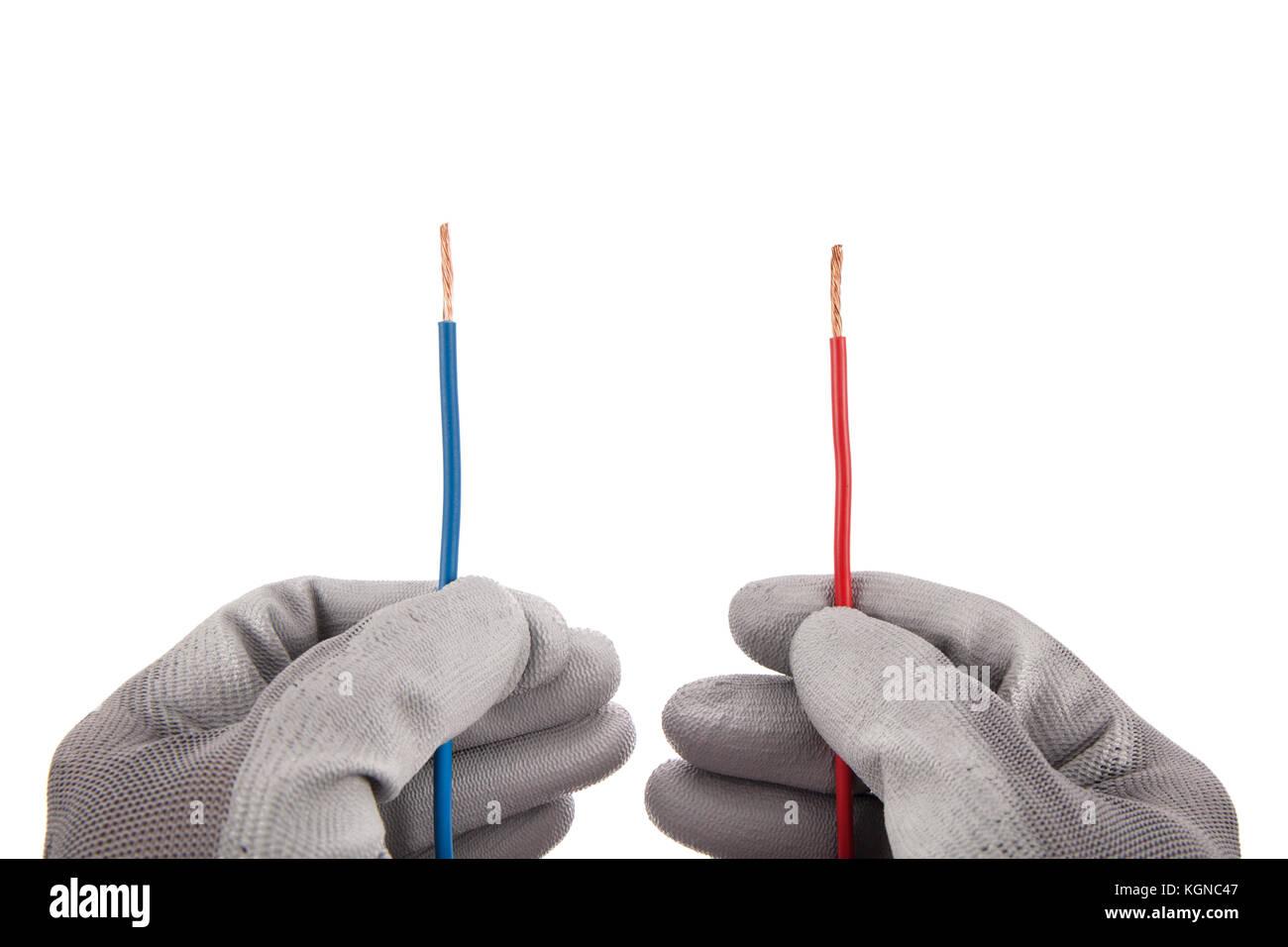 Rot und Blau parallele Drähte in den Händen mit Schutzhandschuhen auf weißem Hintergrund Stockbild