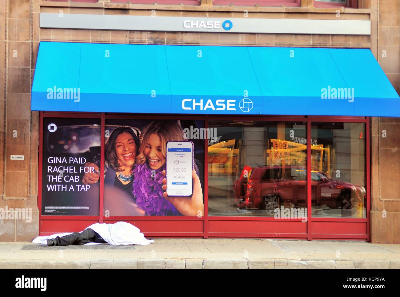 Die sozialen Gegensätze auf einer Straße in der Innenstadt von Chicago als ein obdachloser Mann schläft unter einem Stockfoto