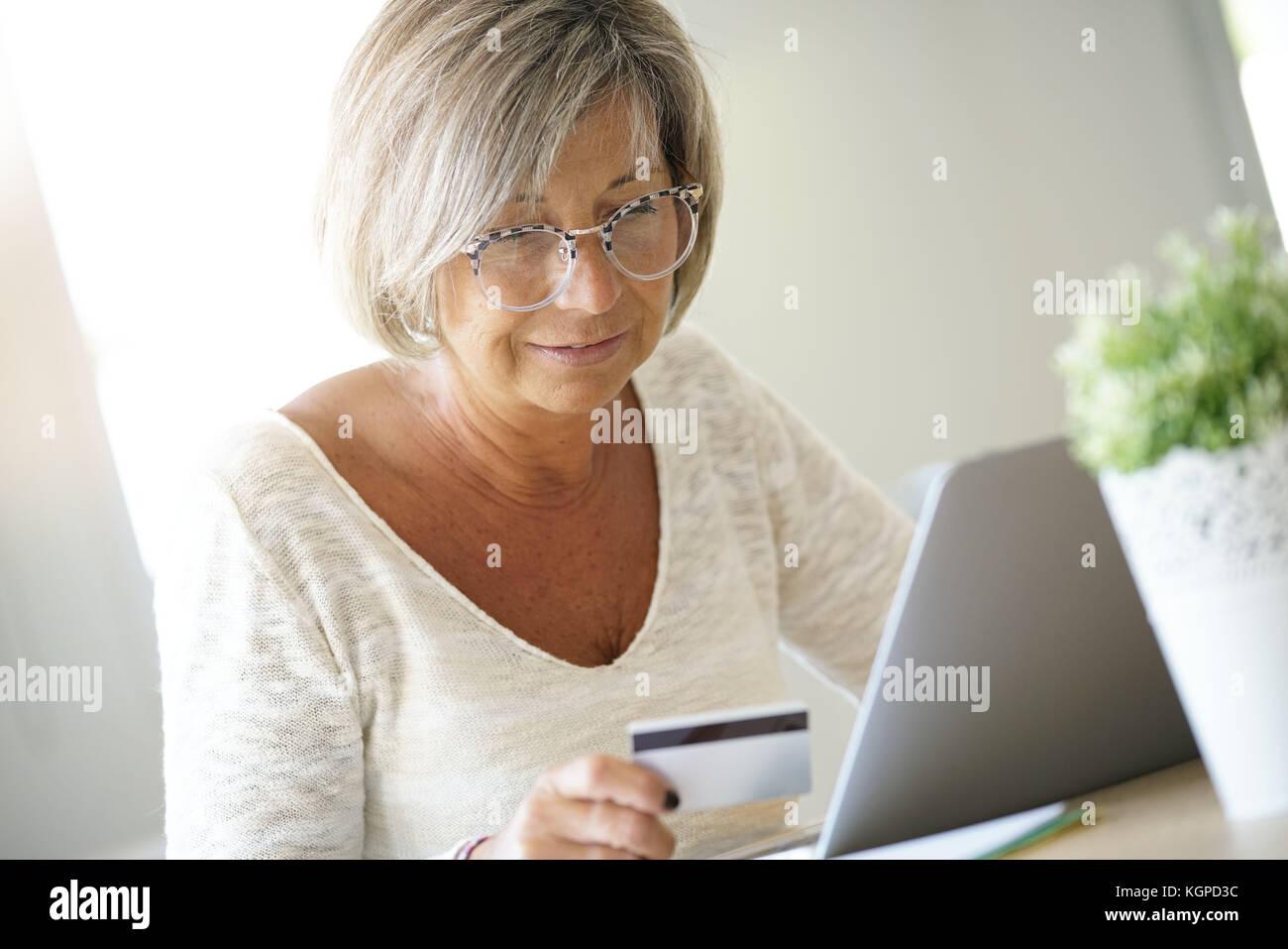 Ältere Frau Kauf im Internet mit Kreditkarte Stockbild