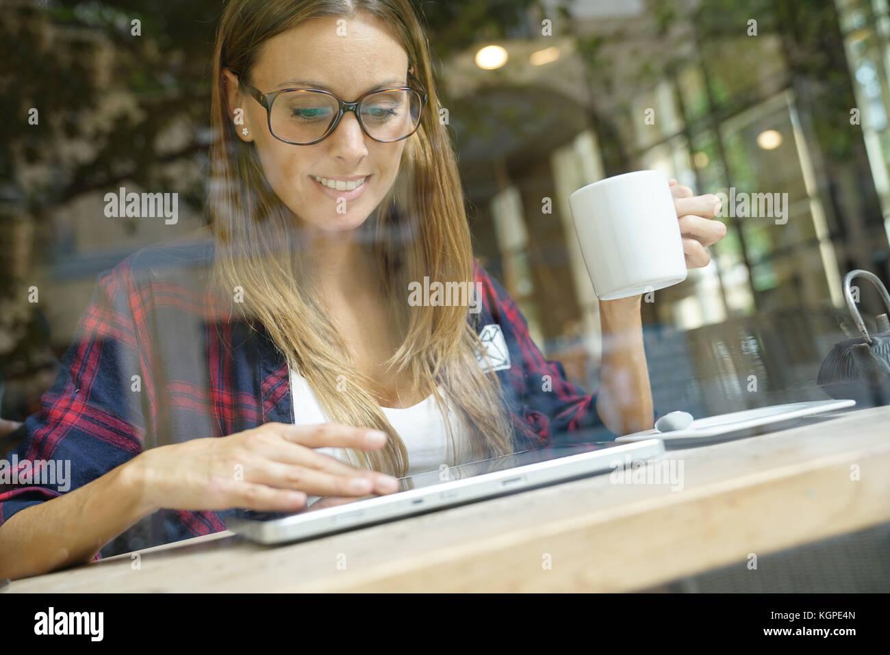 Trendy City Girl in Coffee Shop mit digitalen Tablet angeschlossen Stockfoto