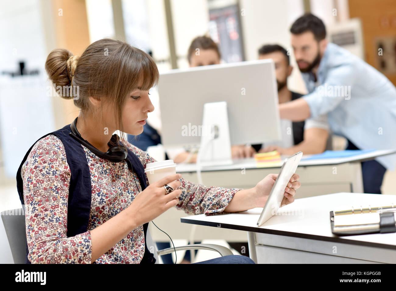 Moderne, junge Frau, die in Büros arbeiten auf Tablet Stockbild