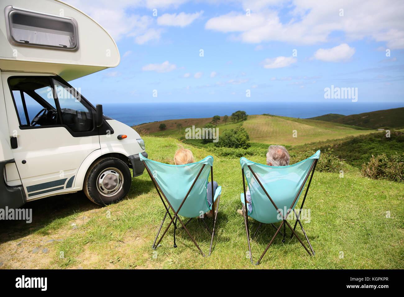 Senior paar entspannende im Camping Klappstühle, Meer Landschaft Stockbild