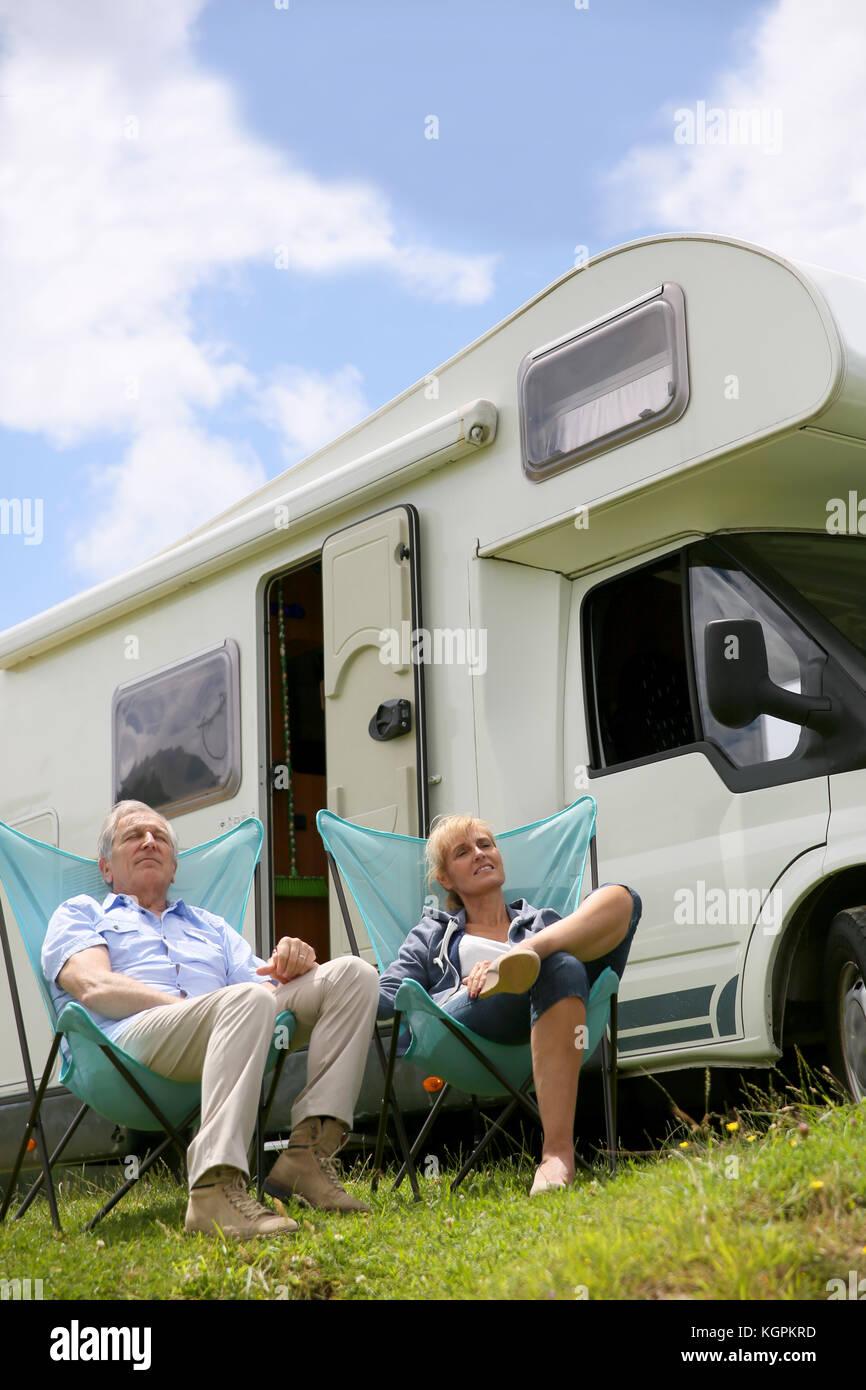 Senior paar entspannende im Camping Klappstühle, Reisemobile im Hintergrund Stockbild