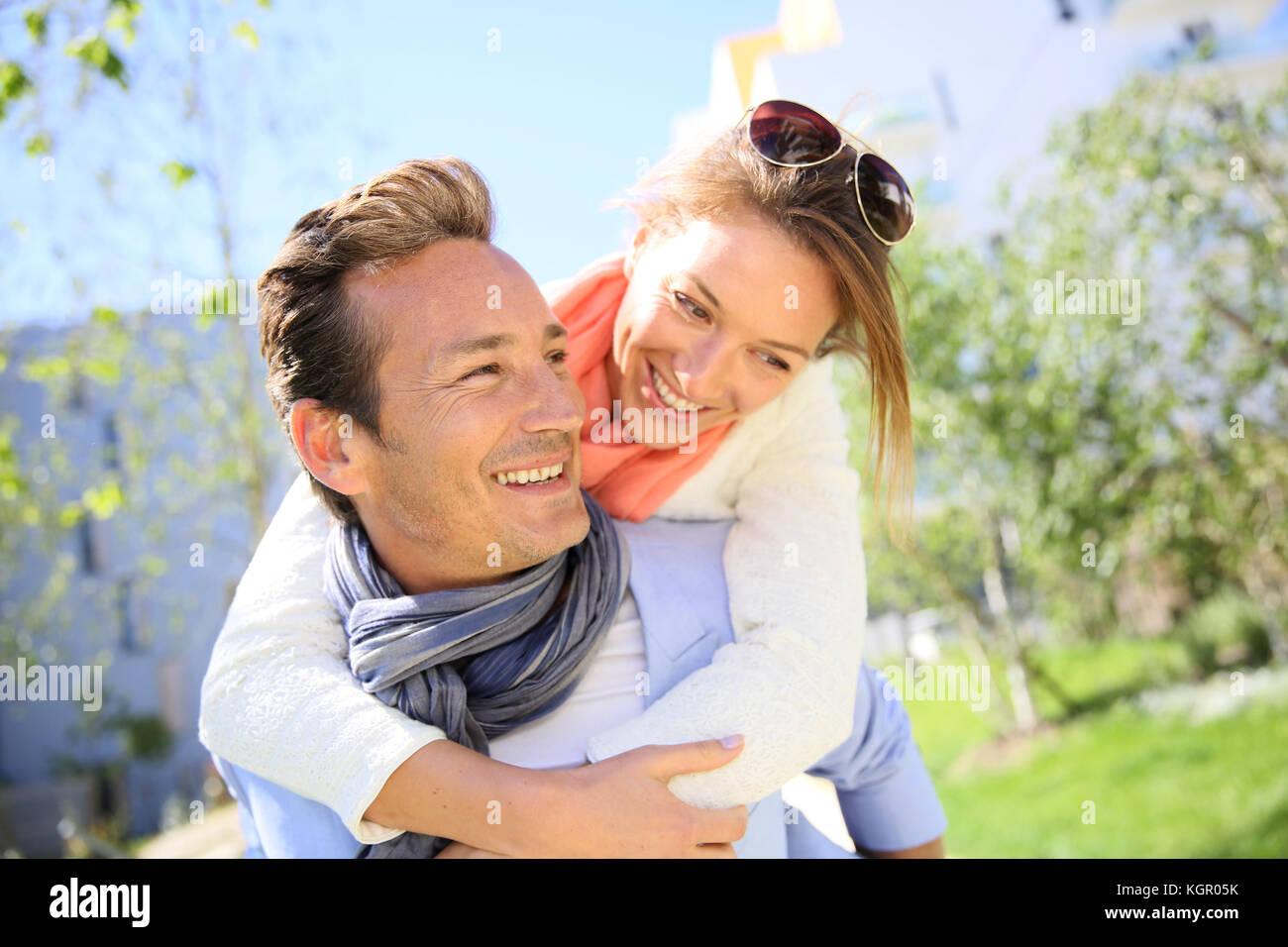 Mann, piggyback Ride zu Frau im Park Stockbild