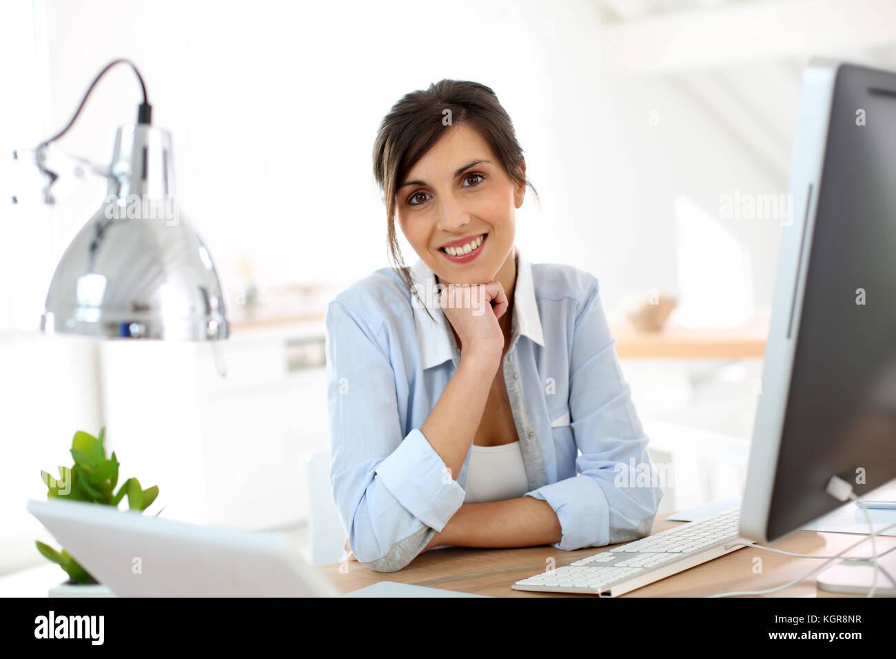 Lächelnd im Büro am Schreibtisch sitzen Stockbild