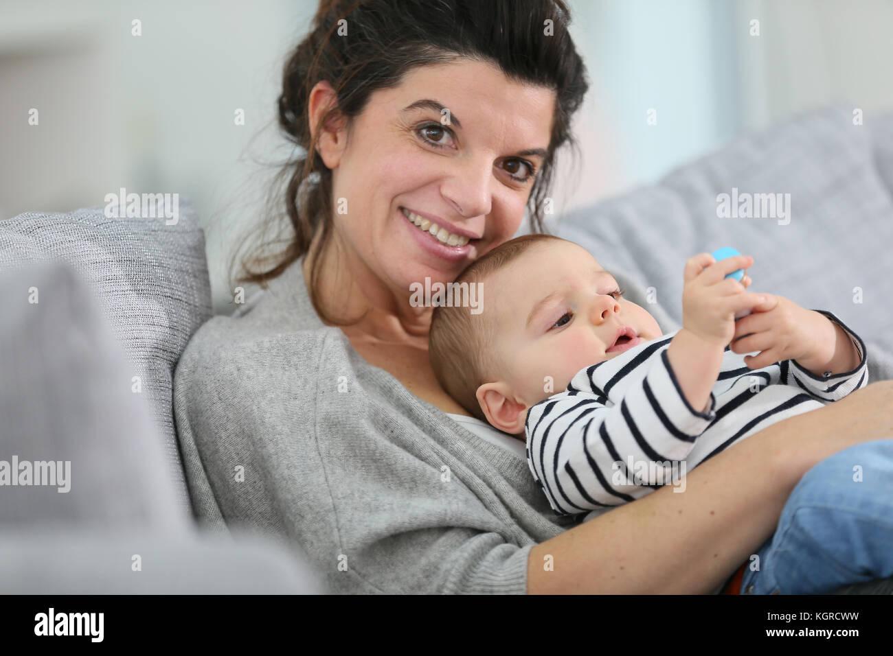 Fröhliche Mutter kuscheln im Sofa mit Baby Sohn Stockfoto