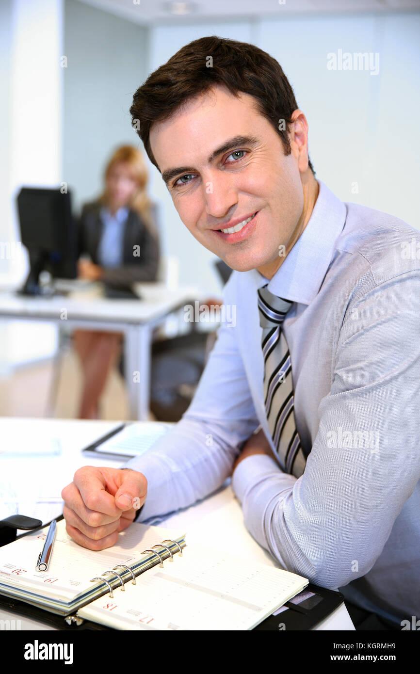 Porträt von lächelnden Geschäftsmann im Büro Stockbild