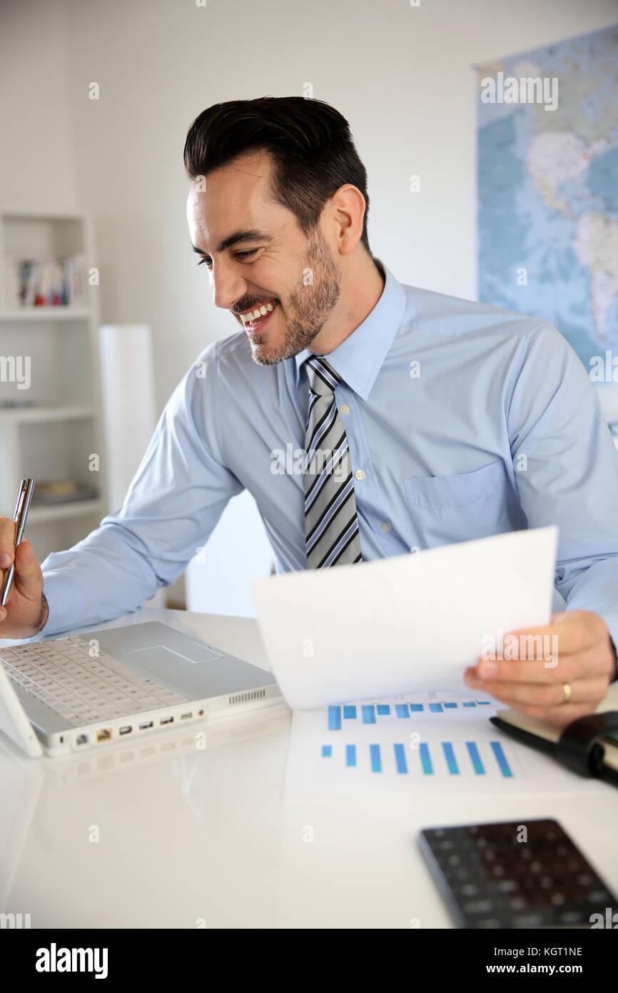 lächelnde Geschäftsmann arbeiten im Büro Stockbild