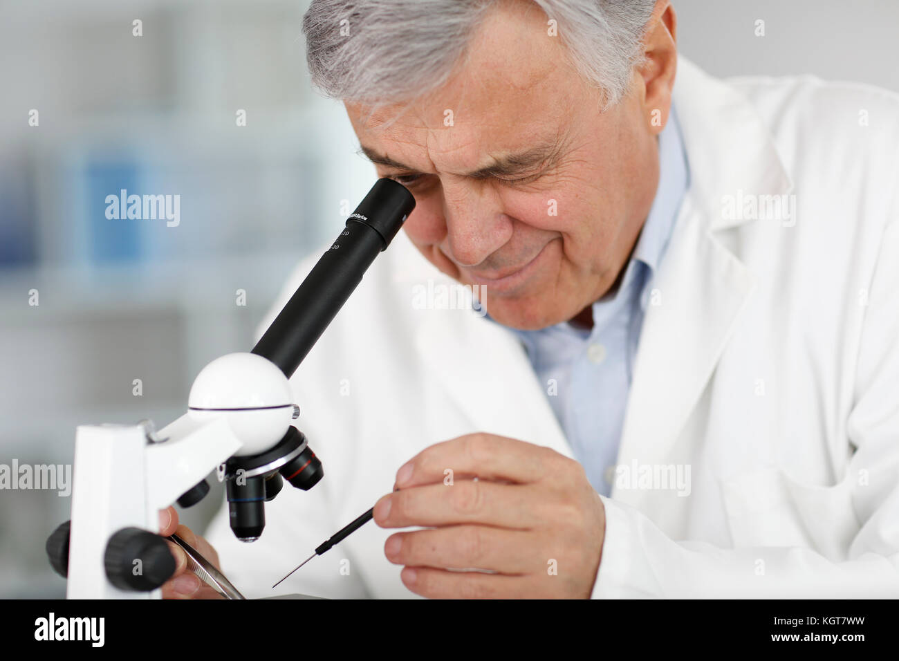 Wissenschaftler im Labor Mikroskop Objektiv durchsehen Stockbild