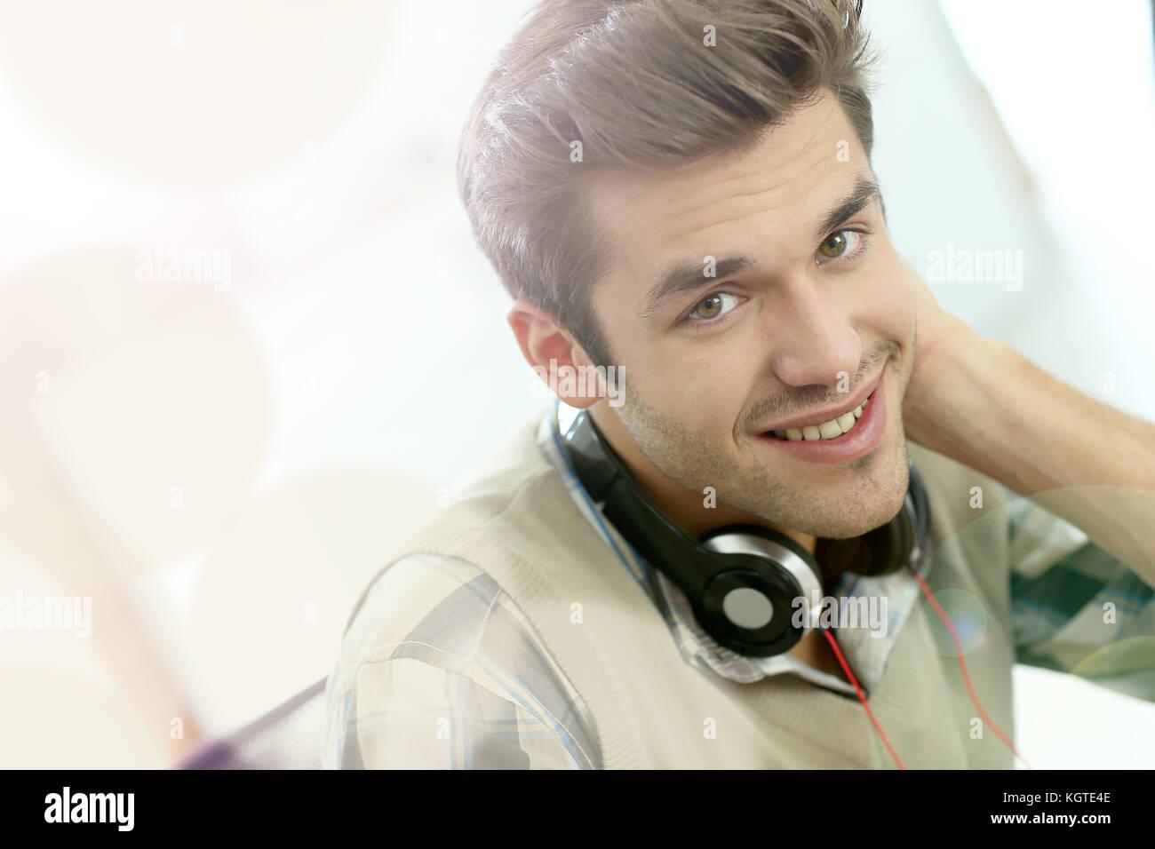 Junge Büroangestellte mit Kopfhörern vor Laptop Stockbild