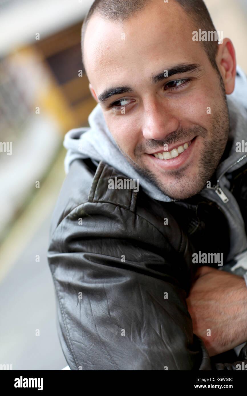 Lächelnden jungen Mann mit Leder Jacke in der Stadt Stockfoto