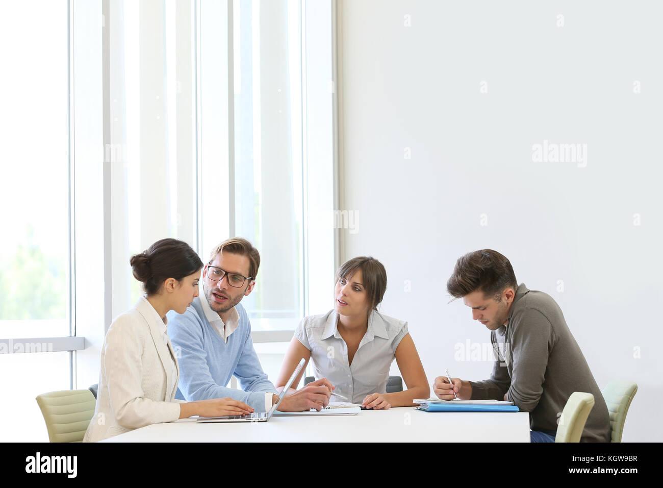 Business Leute, die um den Tisch in der modernen Platz Stockbild