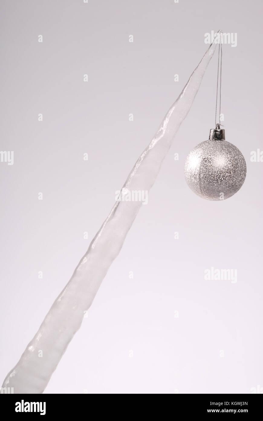 eiszapfen mit einem weihnachtsbaum spielzeug auf grauem hintergrund gefrorenes wasser stockfoto. Black Bedroom Furniture Sets. Home Design Ideas