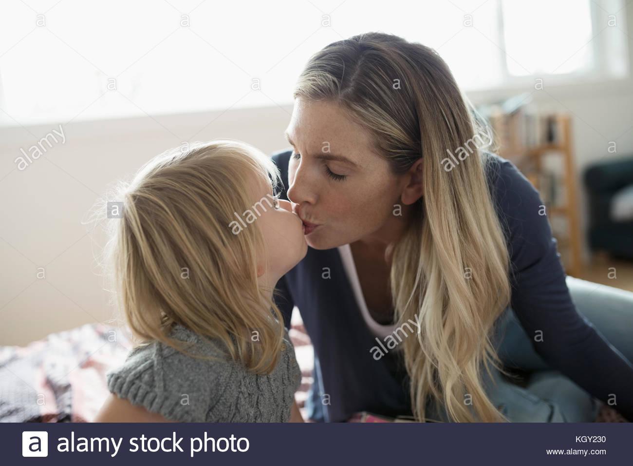 Zärtlich blonde Mutter und Kleinkind Tochter küssen Stockbild