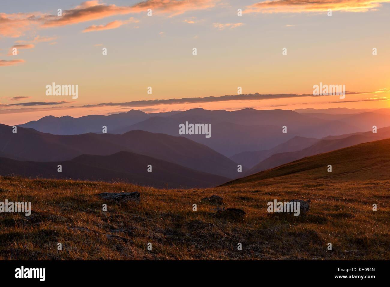 Die malerische Aussicht auf die Berge, die Sonne und die Konturen der Berge im Sonnenlicht bei Sonnenuntergang Stockfoto