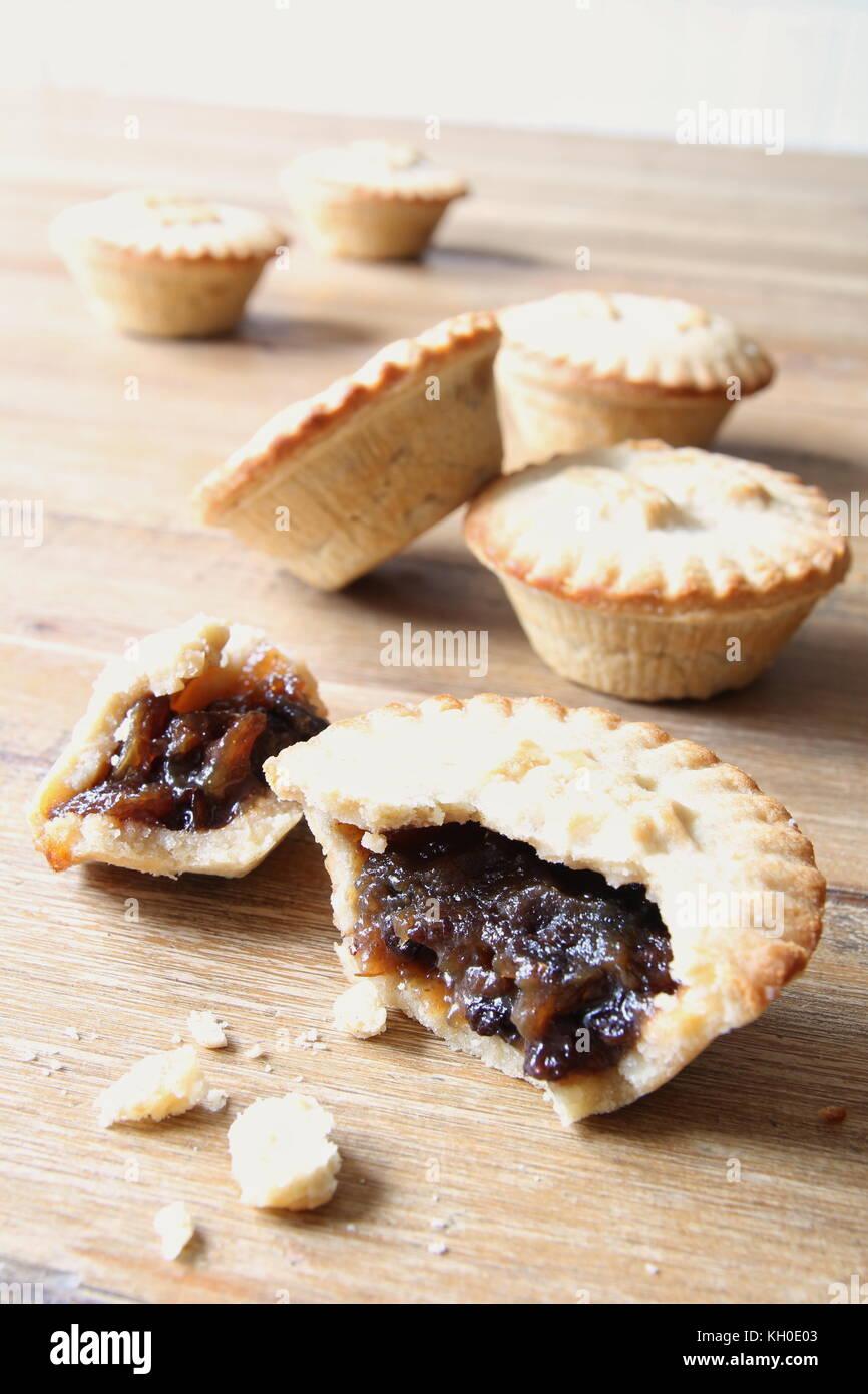 Auswahl von mehreren Mince Pies, einige kaputte öffnen oder teilweise gegessen. Eine traditionelle festliche Stockbild